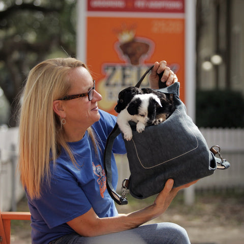 Michelle Ingram owner of Zues' Rescues in New Orleans holds rescued puppies in the Pang Wangle Touring Convertible Backpack