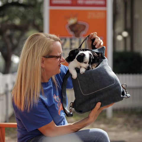 Michelle Ingram owner of Zues' Place in New Orleans carries puppies in the Pang Wangle Touring Convertible Backpack.