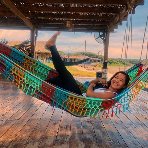 Png Wangle blog Dispatches features Riza Ayson smiling in a hammock kicking up her legs in Playa Venao, Panama.