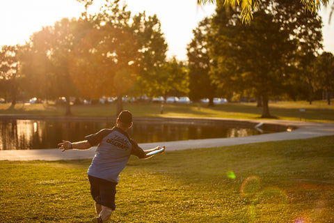 Pro disc golf player Shane Seal launches a disc across a field in Lafreniere Park in Metairie, Louisiana