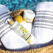 Mademoiselle Provence Lemon and Verbena body lotion for glowing and toned skin. Pictured by the pool in a towel basket with lemon and scrub.