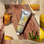 Mademoiselle Provence Lemon and Verbena refreshing and revitalizing hand cream  for healthy, illuminated, glowing skin. Photo collage featuring lemons, flowers, skin, and hand lotion. Made in France body lotion with natural ingredients.