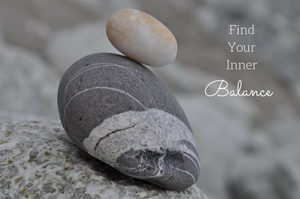 A small white stone balancing on a larger grey stone with words find your inner balance