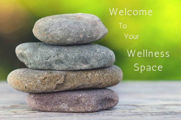 Stack of 4 flat stones with differing tones on a wooden table with blurred green background and words welcome to your wellness space