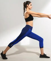 model stretching, Nik Spruill designer, side view, color block legging, navy blue legging, Nik Spruill Brand