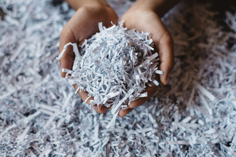 Hands holding shredded recycled paper