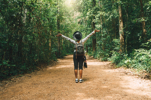 Happy lady walking through rainforest