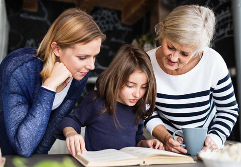 Grandmother, mother, and daughter looking at a elderberry gummy recipe
