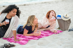 Three friends on the beach sipping out of their HaloVino sustainable glasses.