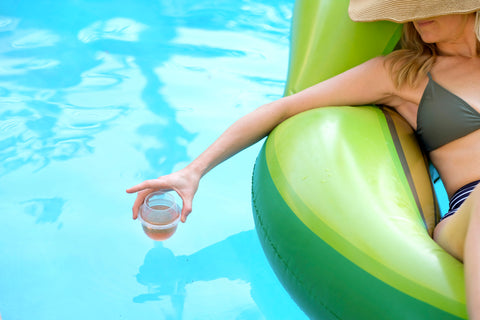 Woman on a pool float holding her HaloVino wine tumbler over the pool.