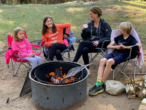 Kids and their family sitting around a fire drinking from HaloVino sustainable glasses.
