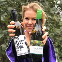 Jessica Bell holding two bottles of wine that are great for HaloVino wine tumblers.