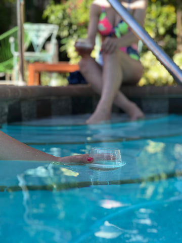 A HaloVino wine tumbler floating on the pool surface.