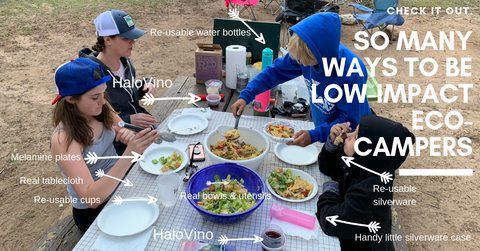 A image of a camping table showing everything that is zero waste, including reusable dishes, HaloVino sustainable glasses, real tablecloths, and more!
