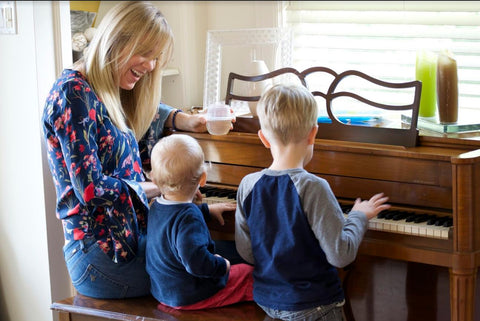 Jessica Bell sitting at a piano with her two children while holding a HaloVino wine tumbler.
