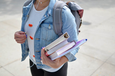 Photo by Element5 Digital on Unsplash. Girl going back to school with books in hand.