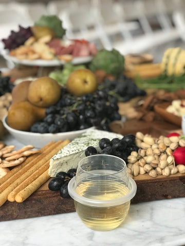 A HaloVino wine tumbler filled with wine in front of a charcuterie board.