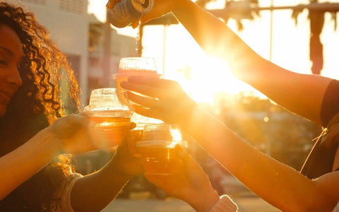 Women standing in the sunset pouring wine into their HaloVino wine tumblers.