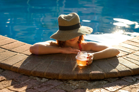 A woman leaning against the edge of a pool with a glass of rose in a HaloVino wine tumbler.