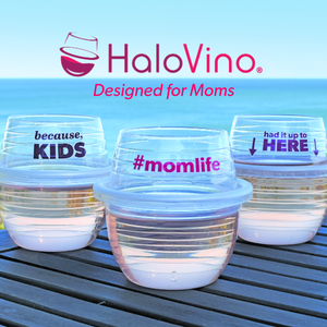 Three HaloVino wine tumblers with sayings for moms sitting on a deck by the ocean.