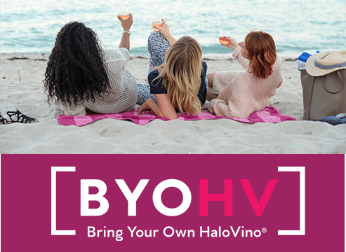 girls drinking wine on a beach with the hashtag BYOHV Bring your own HaloVino