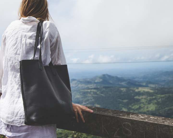 Blonde woman with oversized, black Brave Soles Tote Bag made from eco-friendly materials on her shoulders looking out at the mountains.