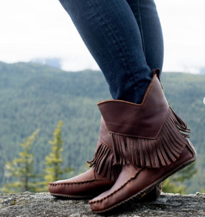 Model wearing Mantiobah Mukluks standing on a log in the forest