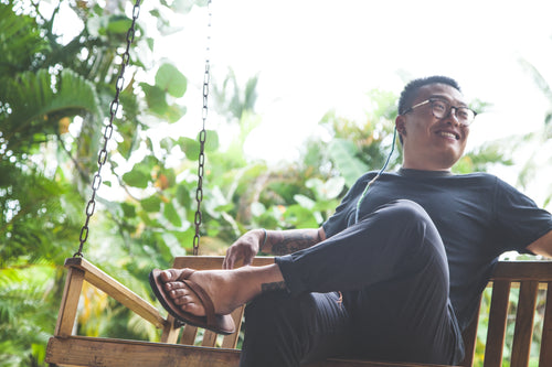 Man Sitting on a bench wearing Brave Soles leather flip flops