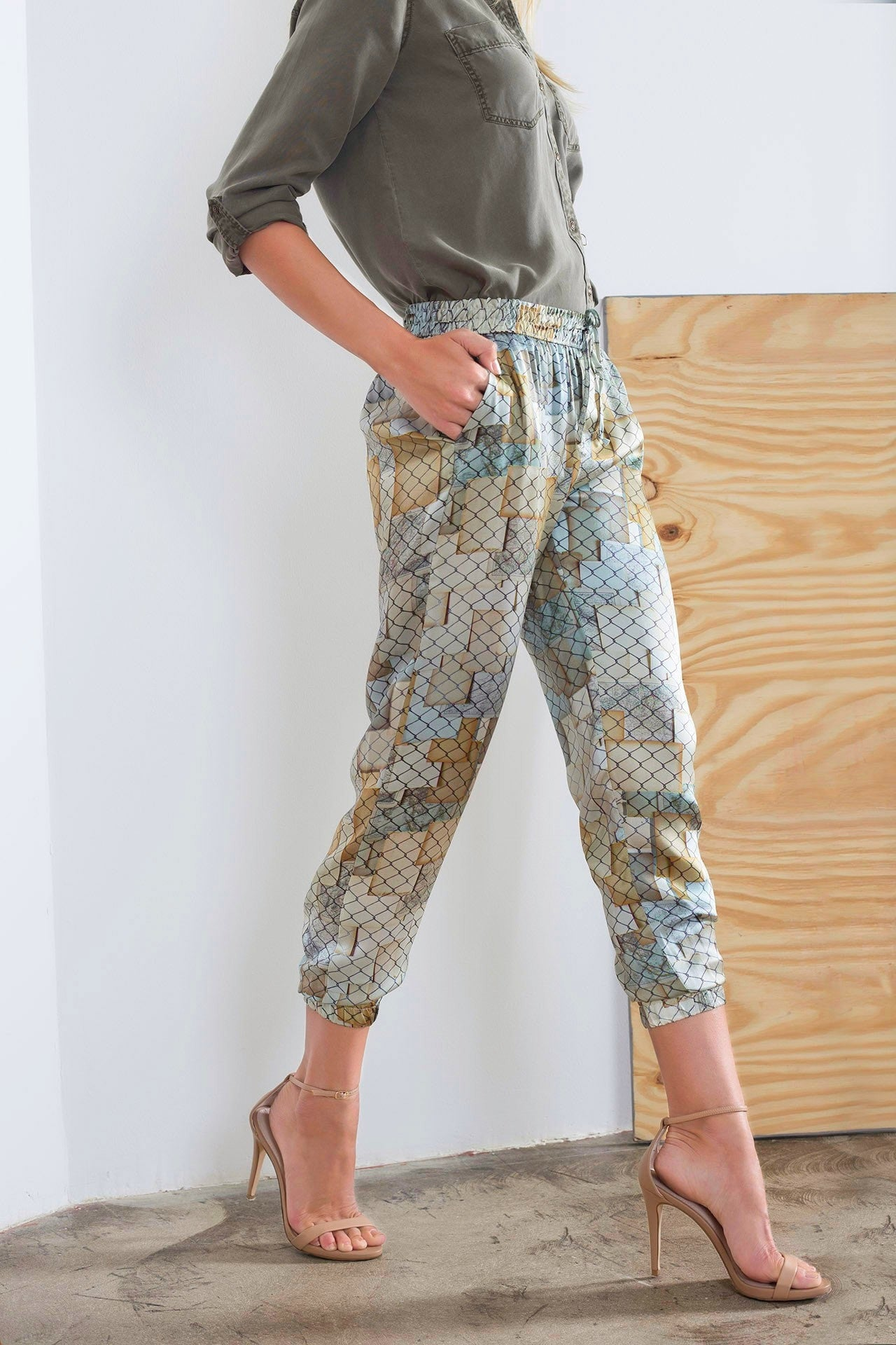 Full detail view of silk jogger pants with golden and silver hues designed by artist Mauro Giaconi