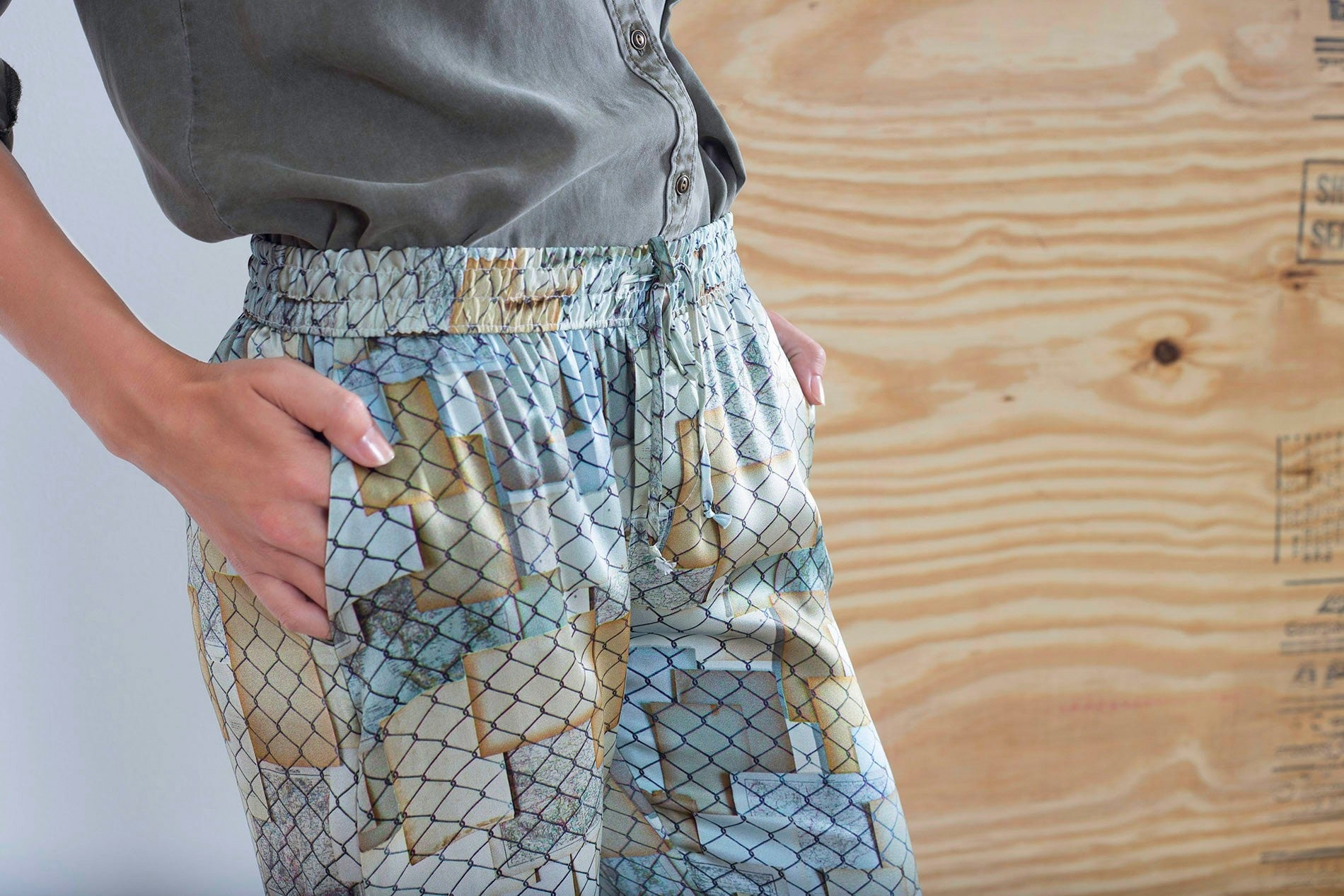 Top detail view of silk jogger pants with golden and silver hues designed by artist Mauro Giaconi