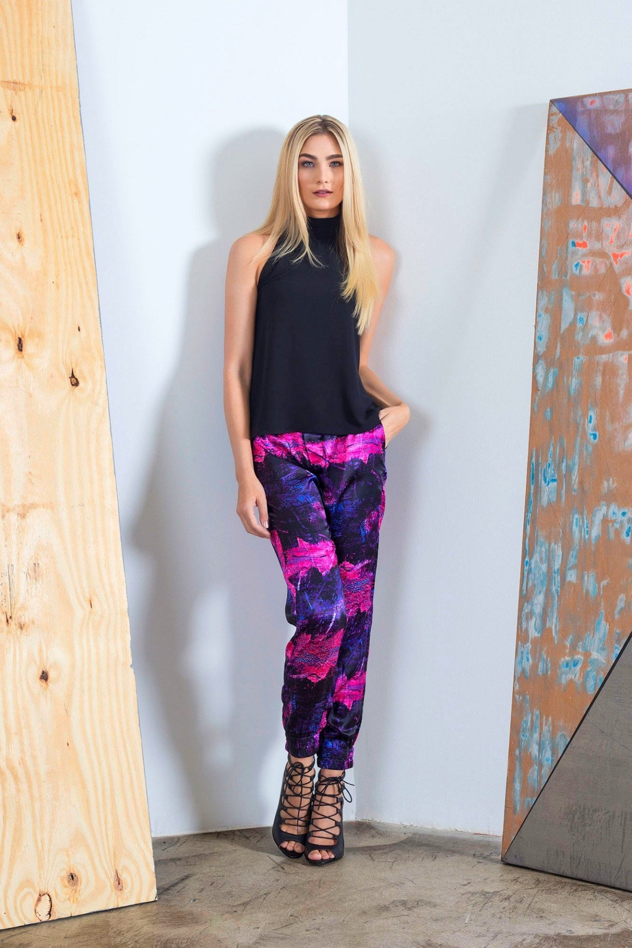 Styled view of trendy women jogger pants with magenta, purple and black art by artist Damian Stamer