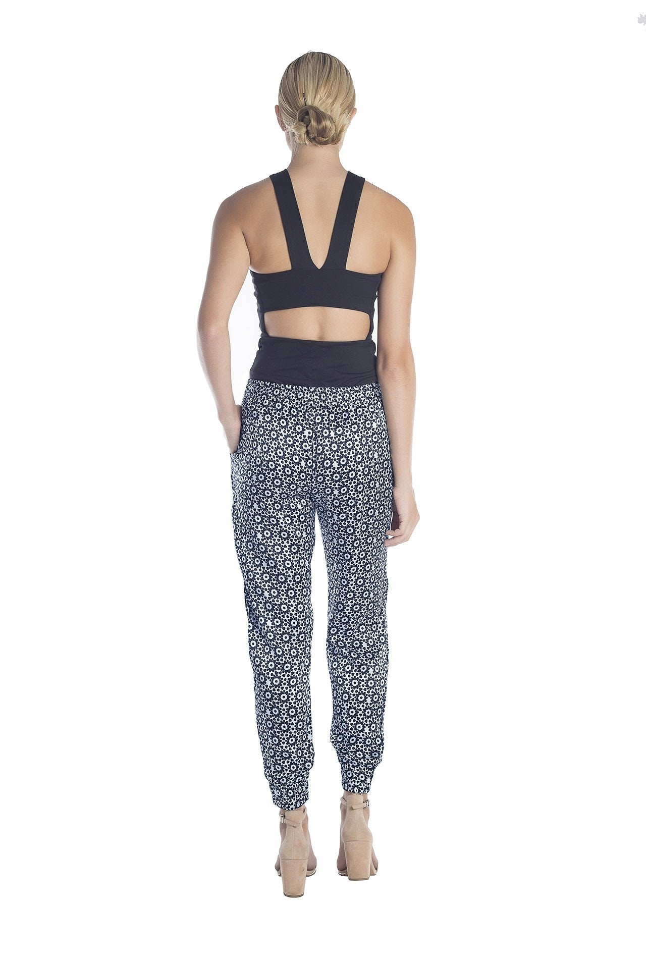 Back view of womens dressy track pants of a black and white mantra designed by artist John Zoller