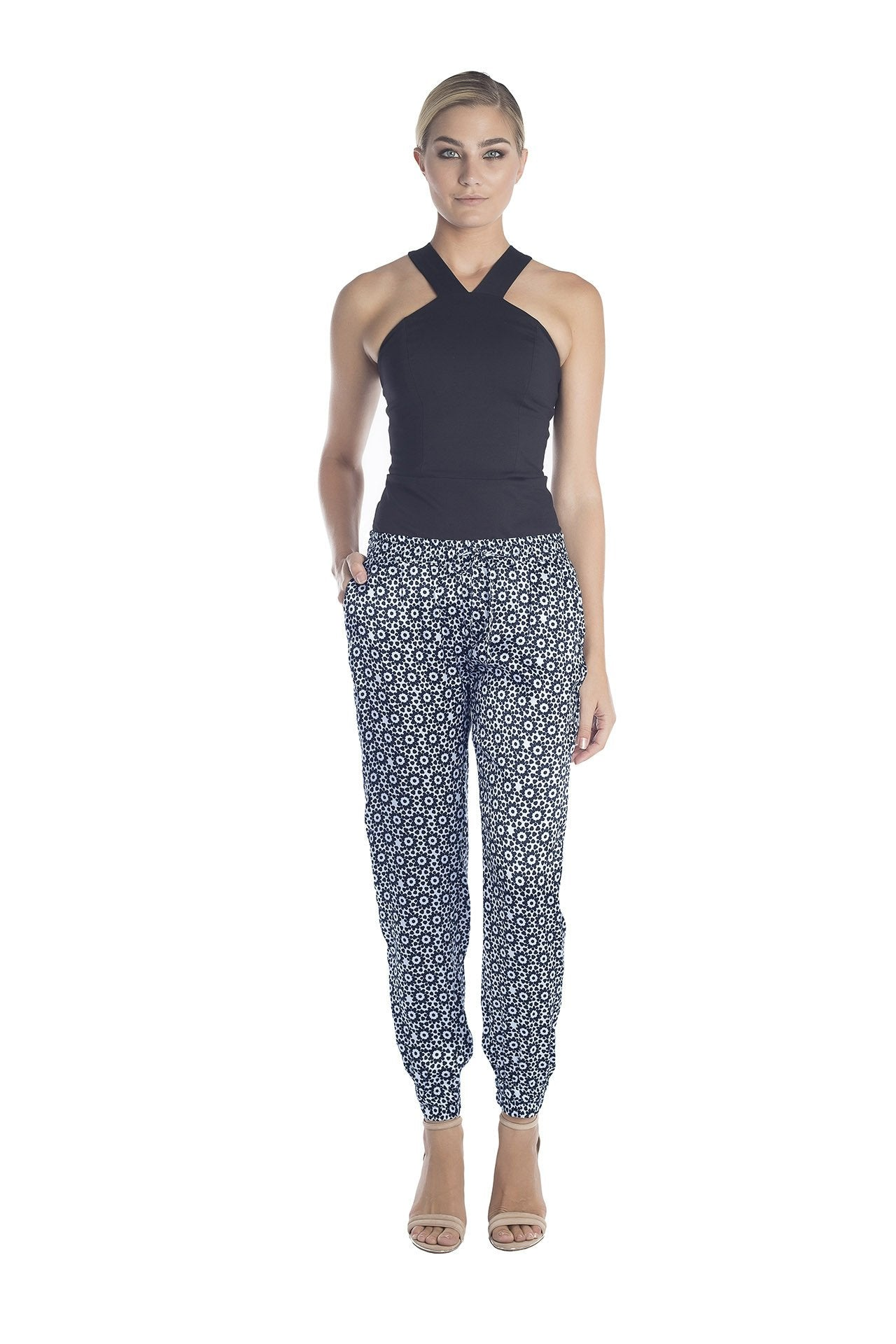 Front view of womens dressy track pants of a black and white mantra designed by artist John Zoller