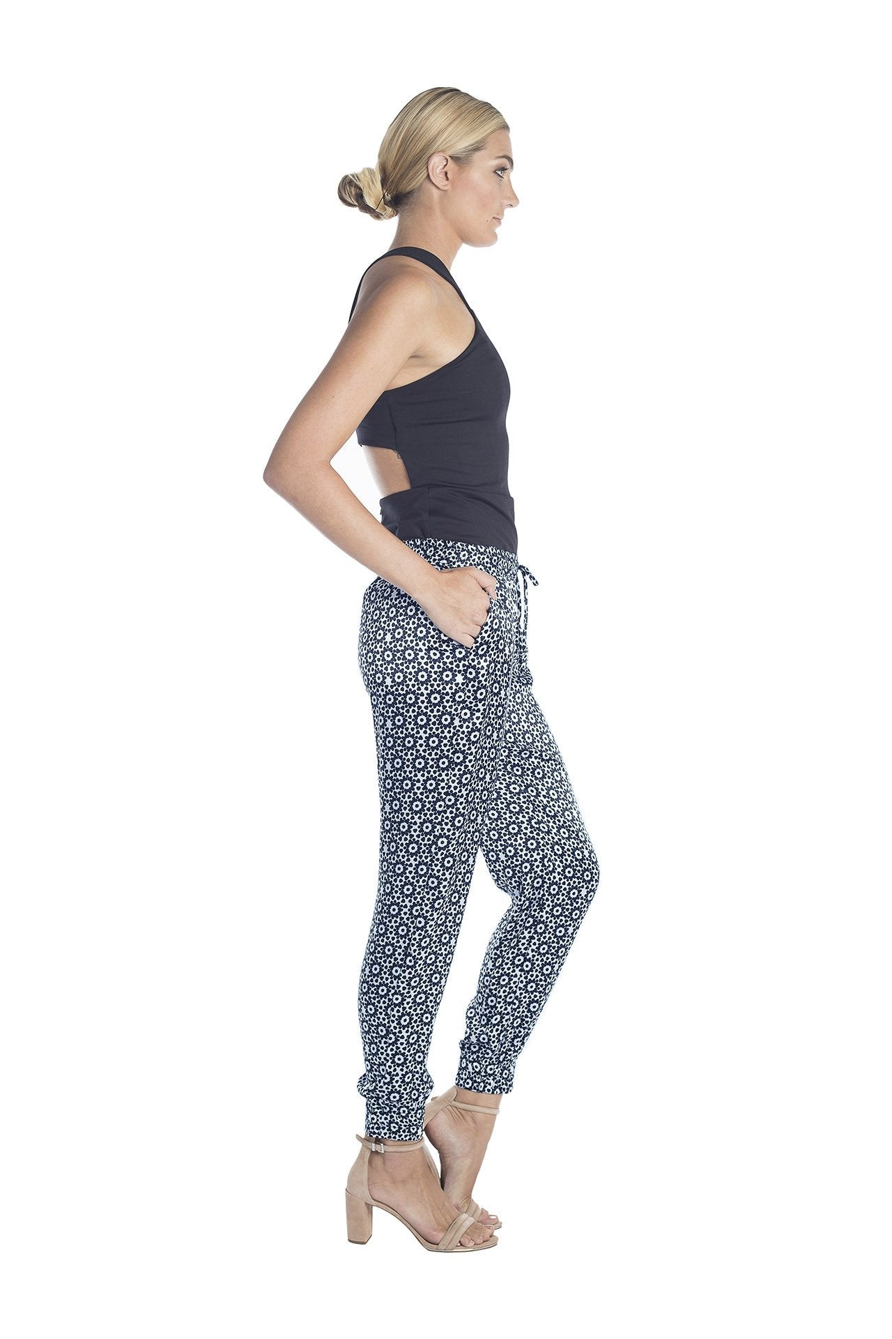 Side view of womens dressy track pants of a black and white mantra designed by artist John Zoller
