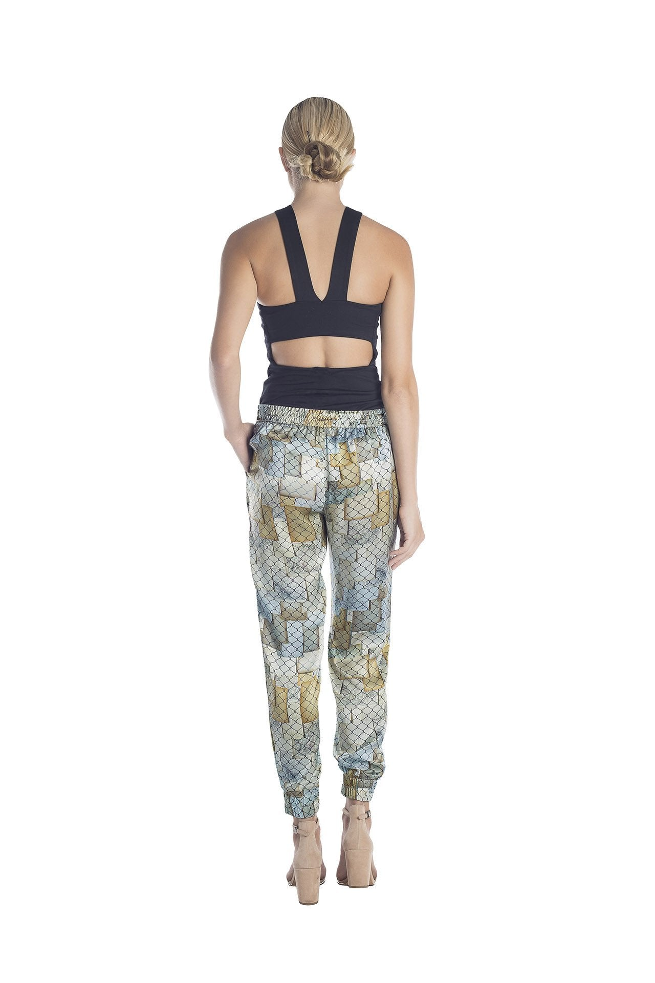 Back view of silk jogger pants with golden and silver hues designed by artist Mauro Giaconi