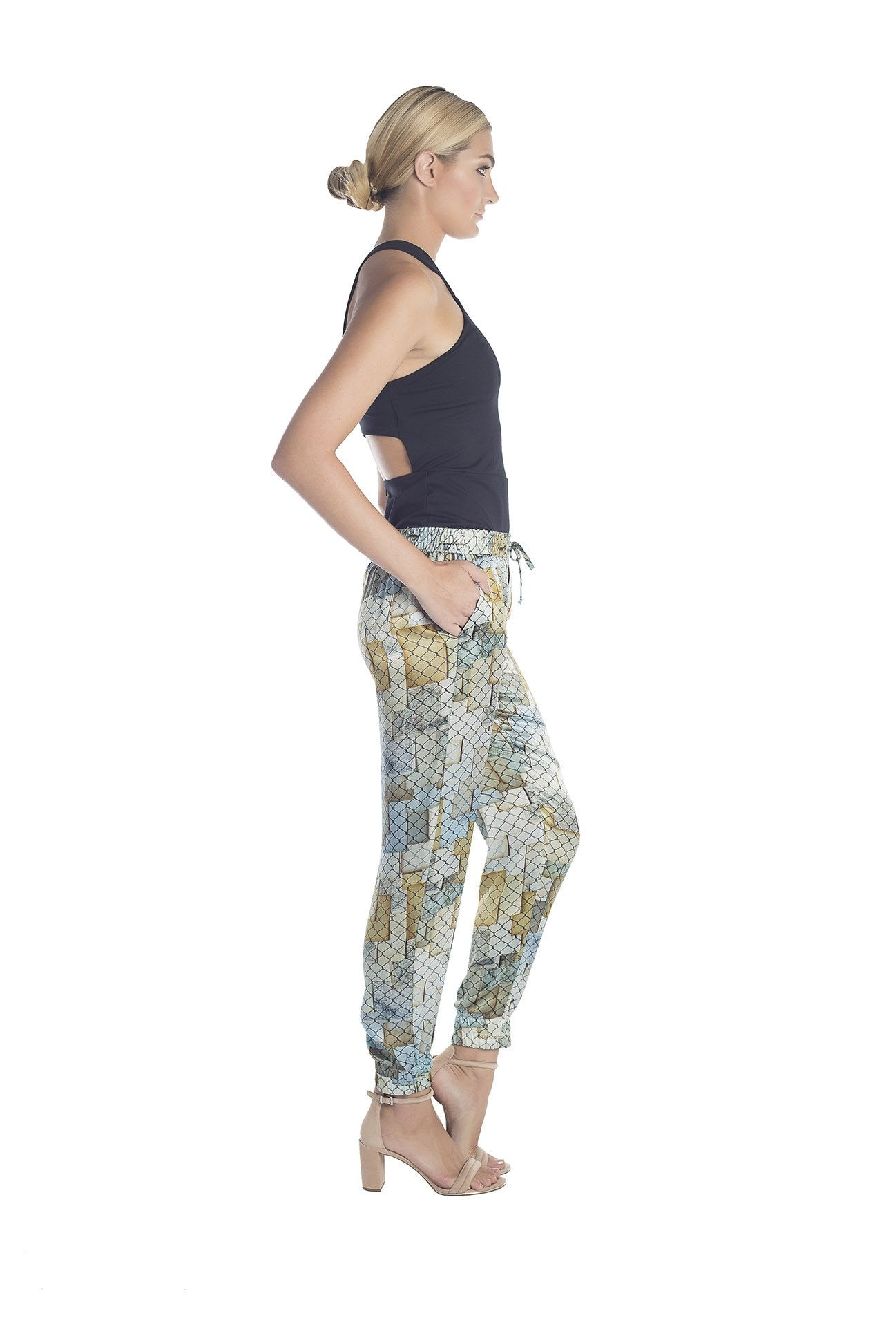 Side view of silk jogger pants with golden and silver hues designed by artist Mauro Giaconi