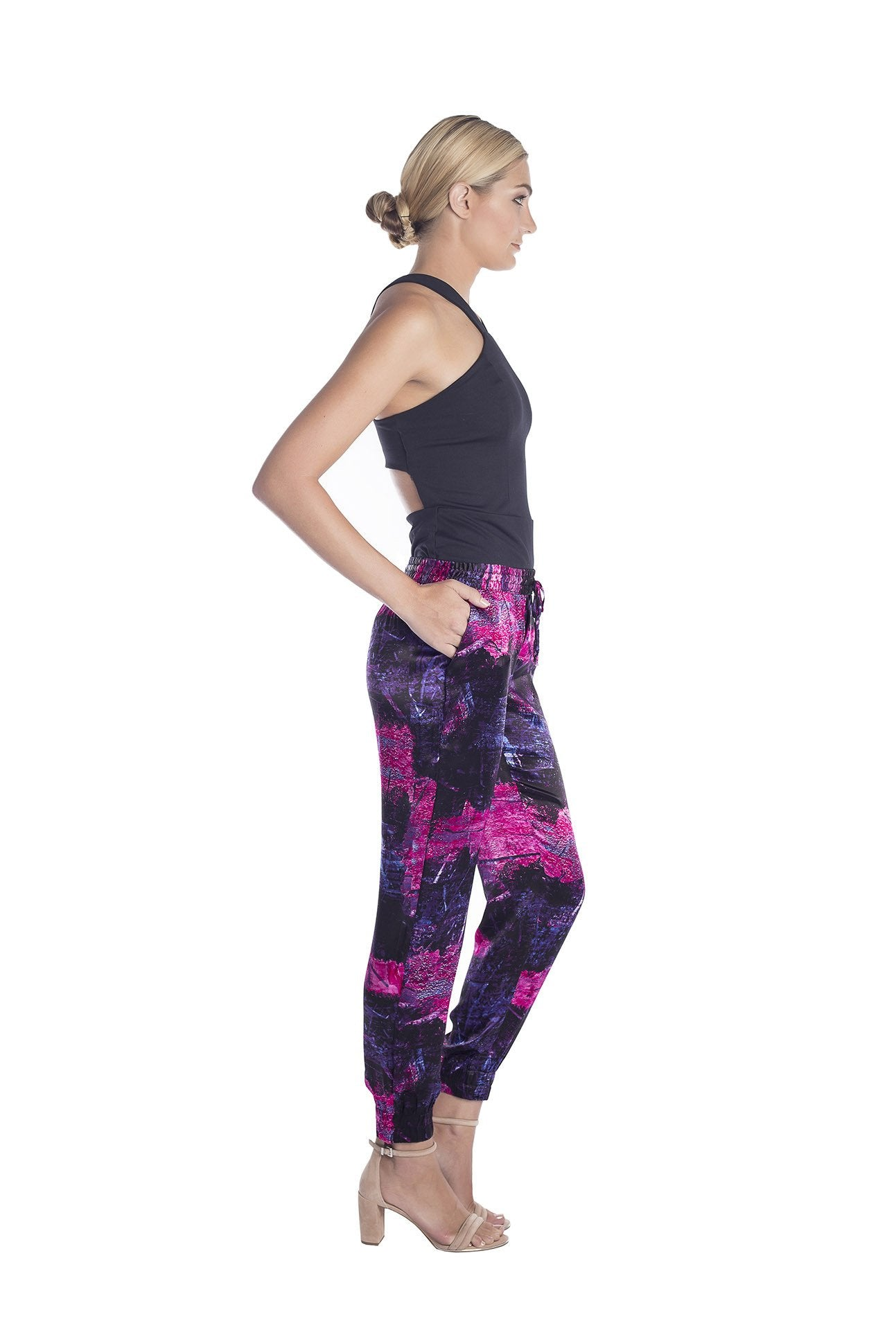 Side view of trendy women jogger pants with magenta, purple and black art by artist Damian Stamer