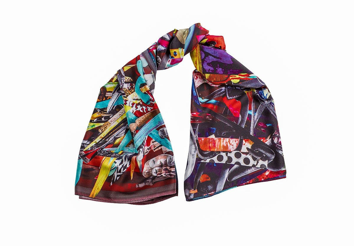 A magnificent 100% silk uniquely designed scarf in multi-colored shades is folded, the wearable art printed detail is very visible.