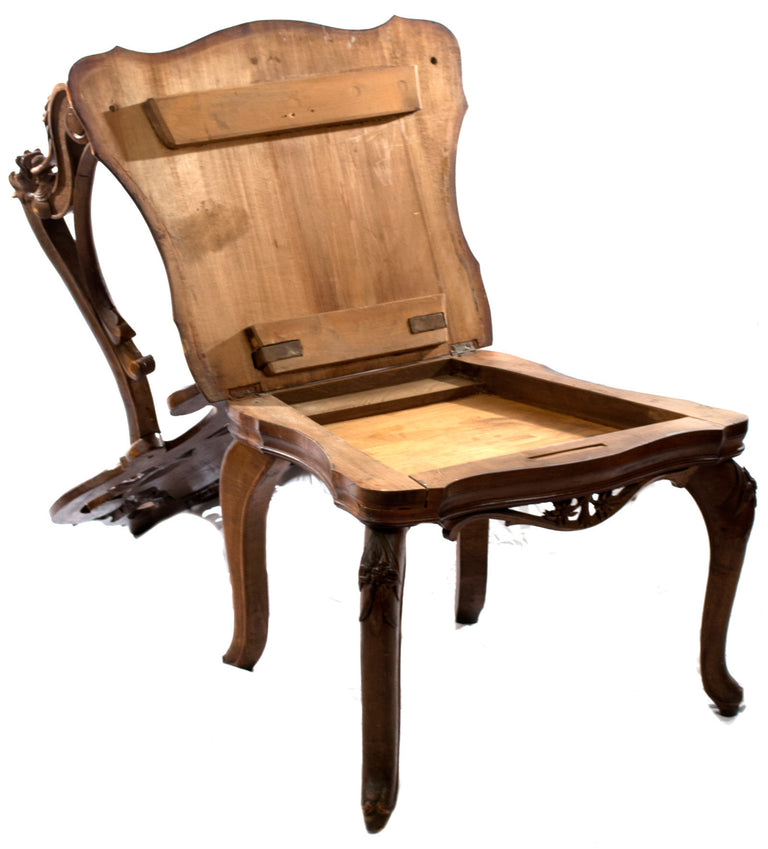 An Elaborately Carved Black Forest Arm Chair with Hidden Compartment