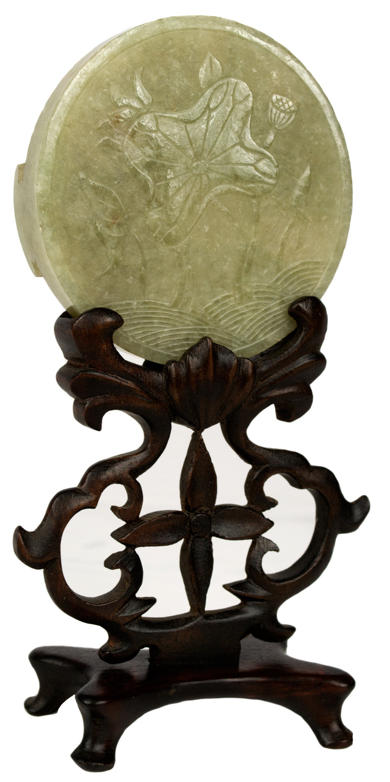 A carved jade disc on an elaborate stand