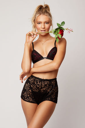 Red and black bralette with black lace and diamonte buckle, lace shorts worn over pants.
