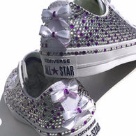 White and purple blinged Converse shoes with bows on the rear seam. Tricked Kicks
