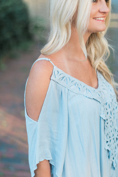 Open-shoulder, crochet-paneled front detail, dusty blue. The Sophie Dress.
