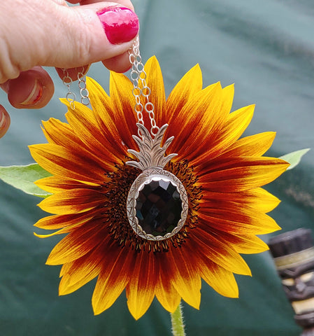 black onyx rosecut pineapple necklace being held in front of a yellow sunflower
