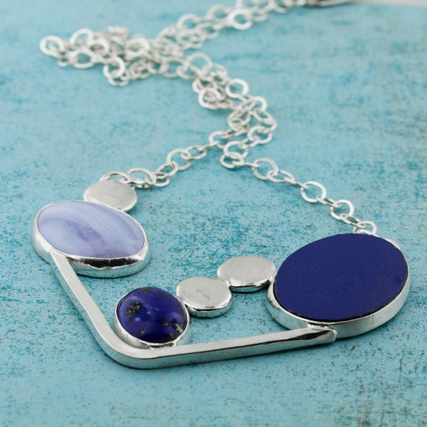 Beautiful abstract modernist necklace in blues featuring blue lace agate, lapis lazuli and laminate on wood.