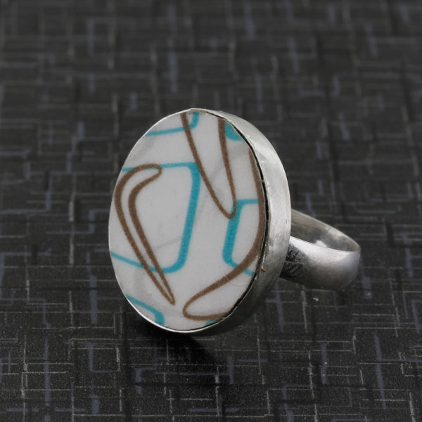 Side view of boomerang laminate ring in turquoise and brown pattern