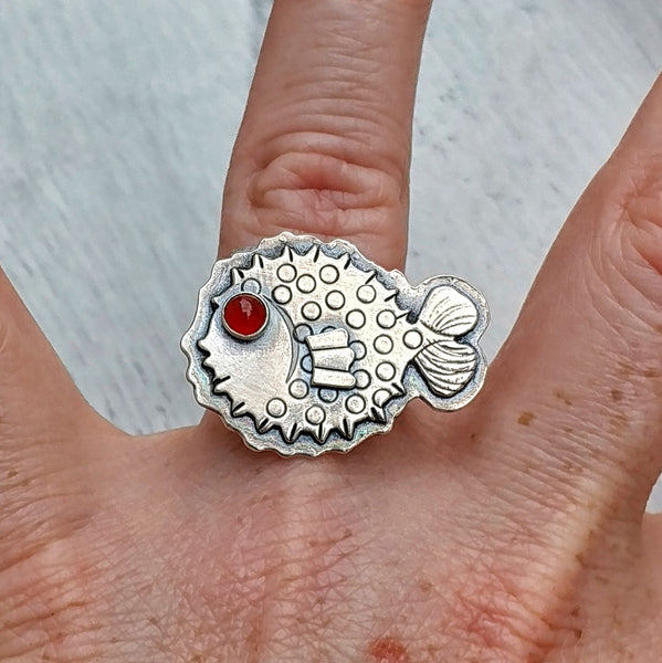 Puffer fish ring on finger with carnelian eye