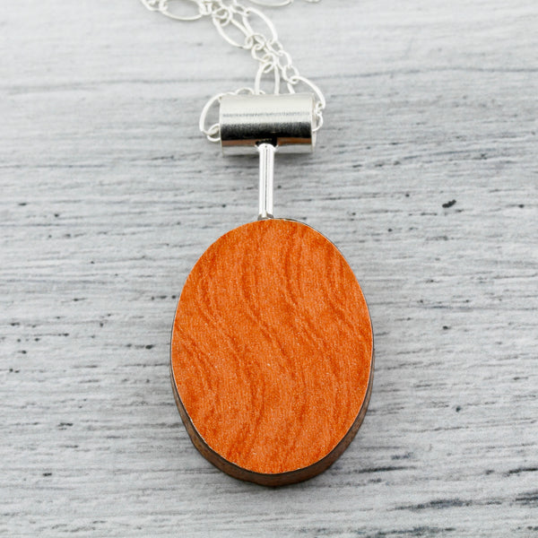Orange side of oval shaped contemporary art jewelry with laminate on wood