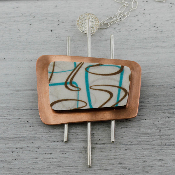 Boomerang shaped laminate in turquoise and white set on a marquee shaped pendant
