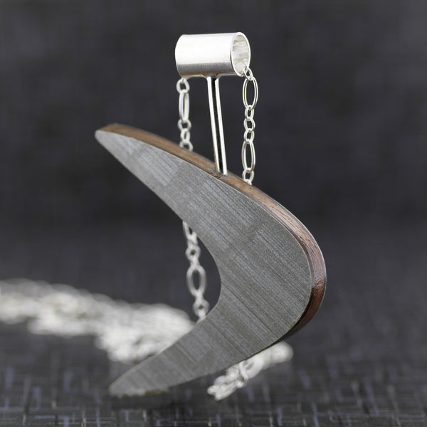 Boomerang shaped laminate on wood necklace.